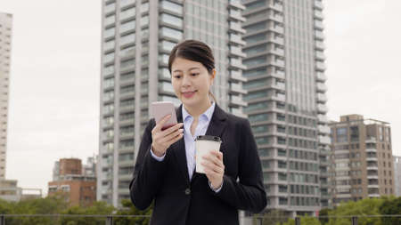 Happy asian businesswoman with start up busienss having walk in city park and typing sms smiling receive good news. young office lady going work in morning with cup of hot coffee. authentic lifestyle