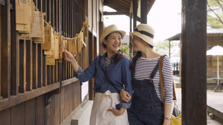 woman tourist show wish card to beautiful friend while sightseeing in japanese temple in osaka japan. young girls having fun laughing reading looking hope board hanging on rope on wooden wall outdoor Stok Fotoğraf