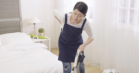 asian housewife woman tired while vacuum cleaning house. wife in apron using cleaner machine on wooden floor feeling back painful. illness frowning housekeeper overworked waist hurting backache.
