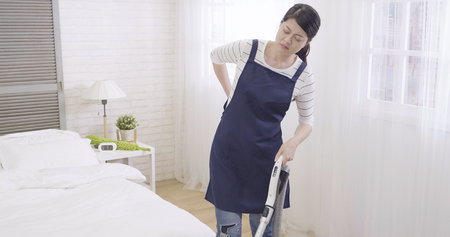 Young japanese household having backache after cleaning and washing floor in bright cozy bedroom. frowning sick asian maid in apron using vacuum machine cleaner indoors working unhealthy housekeeping