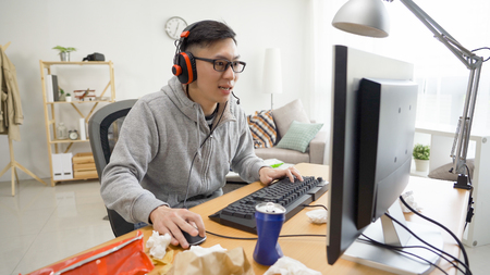 asian guy in headphones playing computer online game on keyboard worried about winning. addiction technology concept. man in eyeglasses looks nervous on monitor pc clicking mouse stay home on weekend