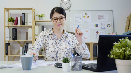 young smiling asian woman worker sitting in creative fashion designer team studio playing having fun with pen hit beating drum as band. cheerful funny girl ceo relax in office alone happy at desk