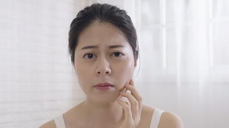 encantadora mujer asiática se mira a sí misma con el punto de vista de la cámara. mujer mirando al espejo toca su rostro comprobando su piel perfecta con sentimiento de insatisfacción. niña preocupada que tiene líneas finas. Foto de archivo