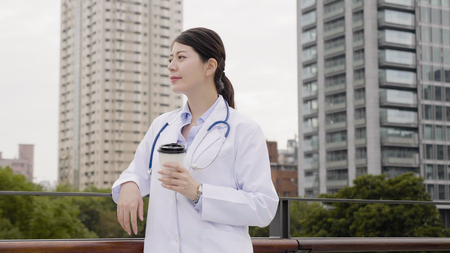 asian female medical staff wearing stethoscope and lab coat relaxing outdoor thinking consider patient situation. doctor woman sightseeing city park with skyscraper in background drinking coffee.