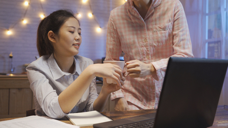 unrecognized woman in pink pajama giving female roommate a cup of water at wooden kitchen table in dark apartment at night. smiling working girl feel sweet holding hot coffee next laptop computer. Stock Photo