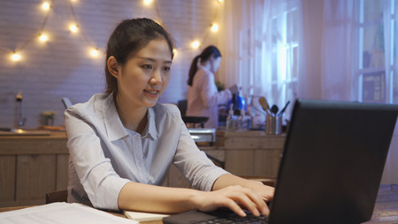 Smiling asian woman freelancer using laptop at home while sitting wooden table. female hands typing on notebook keyboard. girl roommate in pajama standing in kitchen at late night thirsty drink water