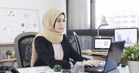 beautiful muslim business woman startup business sitting in office typing on laptop. Banco de Imagens - 124936503