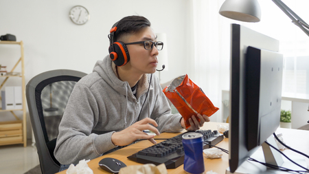 Concentrated young asian man in casual clothing using computer and eating potato chips while spending time at home.