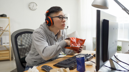 asian chinese man eating potato chips while having fun leisure spend time on computer game.