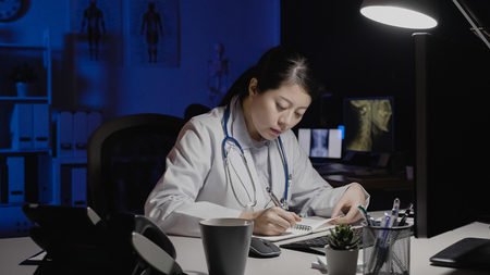 asian female doctor writing on notepad in medical office.