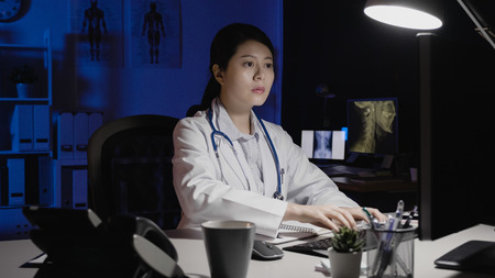 female medical nurse in lab coat concentrated typing computer keyboard in dark clinic office.