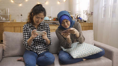 Obsessed diverse female friends roommates with smart phones ignoring each other sitting on couch at home. Reklamní fotografie