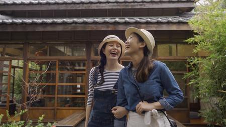 smiling asian girls tourists walking close in japanese style garden having fun together.