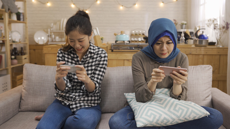 friendship technology home concept. two smiling multiracial female friends with smartphones in kitchen.