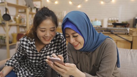 Two cheerful and beautiful multi ethnic girls sitting together on couch watching video on mobile phone.