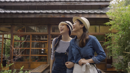 two cheerful women tourists in straw hat visit japanese temple in kyoto japan.