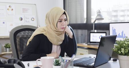 elegant islam woman manager worried face frowning while sitting at desk working.