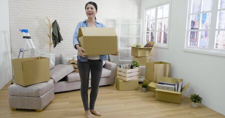 Young asian woman moving into new apartment holding cardboard boxes with belongings.