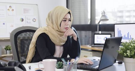 Serious concerned young islam business woman look on laptop screen in deep thought sitting at workplace in modern office.