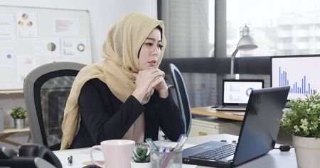 Frustrated tired arabic business woman reading document online with bad news on laptop. Stock Photo