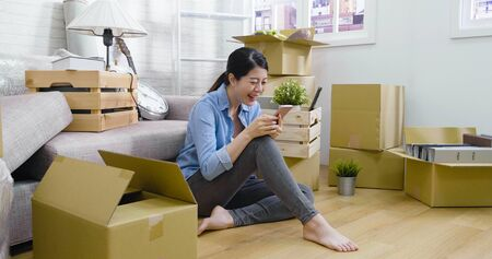 Packed cardboard boxes with woman sitting on wooden floor leaning on sofa in living room.