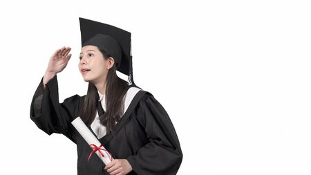 beautiful graduate asian girl in mantle keeps in hands graduation diploma and look up on white background. 写真素材
