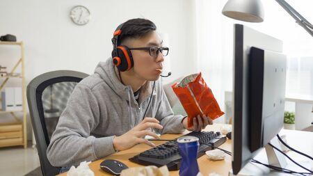 asian guy in grey sweatshirt eating snack and surfing internet watch anime cartoon.