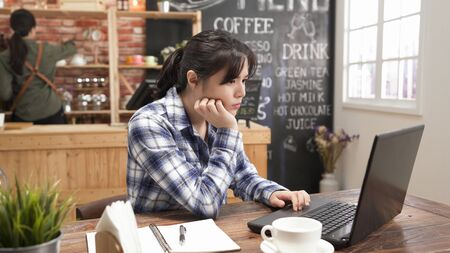 Young attractive asian japanese woman looking thoughtfully on laptop.