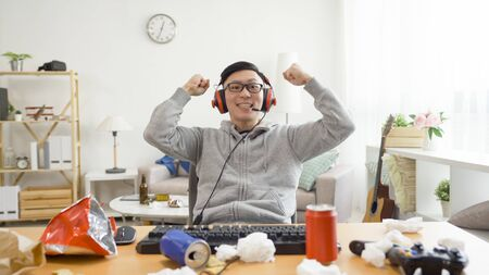 asian male gamer winner screaming and gesturing for a victory on computer sitting at desktop pc with messy dirty apartment.