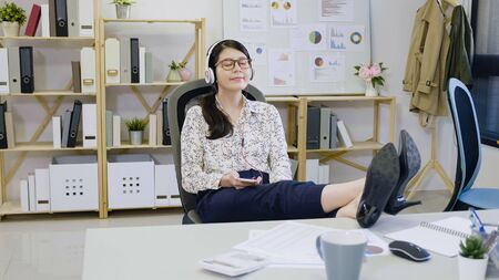 Relaxed happy woman worker dreaming and holding legs on table in modern workplace. 写真素材 - 124942865