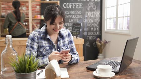 asian business woman in casual wear typing text message on smart phone in cafe bar.