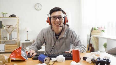 homebody guy smiling looking at camera as computer screen wearing headphones excited emotion.