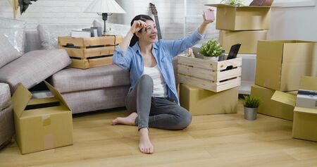 cheerful smiling woman make self portrait sitting on wood floor in bright modern apartment. Stock Photo