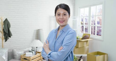 beautiful young asian korean woman moving new home surrounding by cardboard boxes looking at camera and smiling standing in living room.