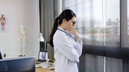 Side view of beautiful young woman doctor in white medical gown keeping hand on chin and thinking concentrated by window.