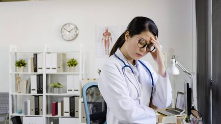 asian female doctor suffering headache being stressed wearing white lab coat.