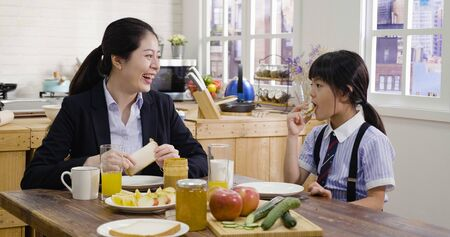 happy asian chinese parent in professional classic business suit smiling at daughter and having breakfast.