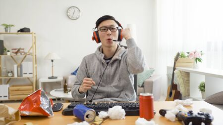 gaming and entertainment concept. happy asian guy homebody playing video game at home in dirty place living lifestyle. 写真素材