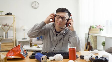 young asian handsome man grabbing headphones on ears while suffering from loud music. 写真素材