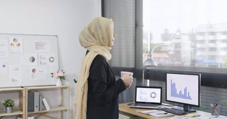 side view adult muslim businesswoman ceo standing at desk in modern office with cup of coffee. elegant arabic woman looks out of window and contemplates the city and skyscrapers. tea break lifestyle.