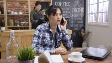 Frowning puzzled asian businesswoman using mobile phone in cafe bar. Serious pensive female advisor checking and talking to customer on cellphone in coffee shop. Personal freelance manager concept.