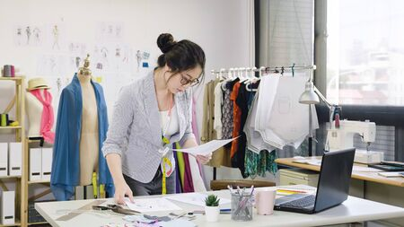 elegant female designer working on laptop and sketching at desk in studio. young woman fashion worker in workshop looking examining at paper of new collection checking with mannequin standing behind