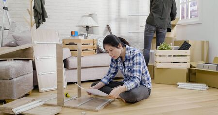 elegant woman reading furniture assembly instructions and sitting on floor in living room.