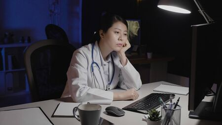 Exhausted young woman doctor at office desk working late at night staring at computer screen in hospital.