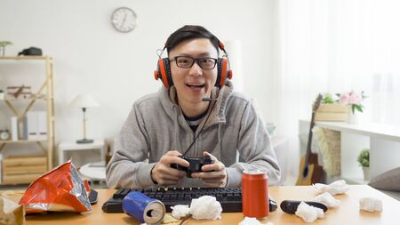 Portrait of attractive asian young man college boy student holding joy stick and playing video games.