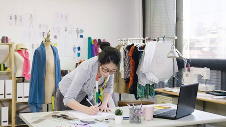 Fashion designer working on designs in studio. asian female employee small start up business owner in office drawing on sketches of new season spring collection on desk. beautiful lady in glasses.