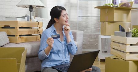 happy young asian chinese woman pensive holding credit card and smiling thinking while using laptop computer in new home sitting on floor surrounding by cardboards boxes in living room joyful move.