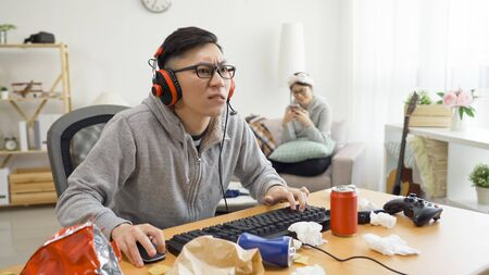 frowning nervous asian handsome man sitting at messy desk playing online computer video game in dirty apartment. cute casual girlfriend in background sitting on sofa joyful using mobile phone social.