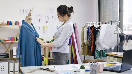 Asian tailor adjusts garment design on mannequin in modern workshop.