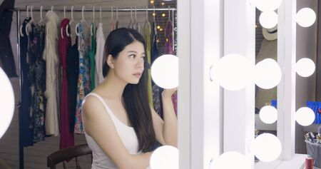 Young asian woman celebrity sitting at makeup table looking reflection in mirror. 写真素材 - 127743524